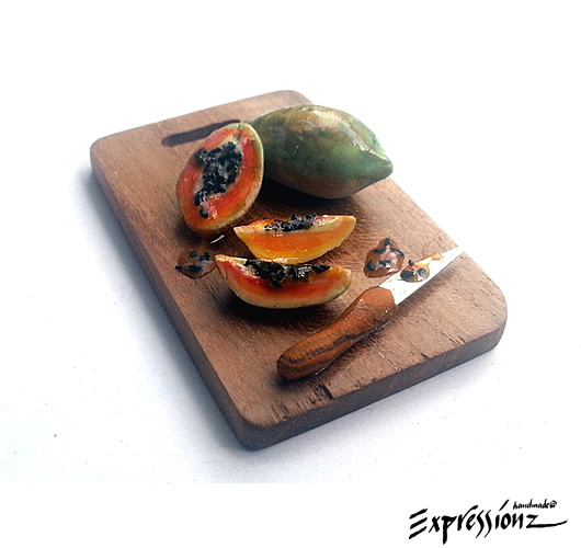 Miniature Papayas on Wooden Board with knife